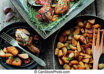 Roasted chicken legs with fried potatoes chips with herbs