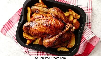 Roasted chicken or turkey with potatoes in black steel mold...