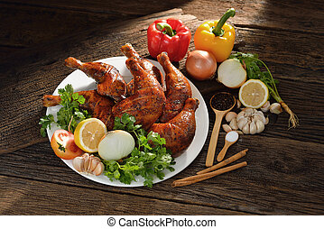 Roasted chicken with ingredients on wooden table