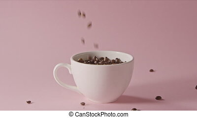 Roasted coffee beans are pouring into ceramic cup and on a ...