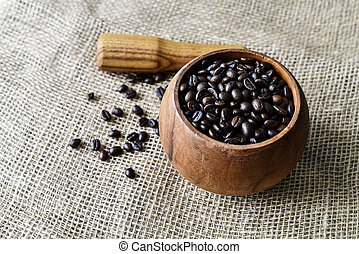 Roasted coffee beans in a wooden mortar on the burlap