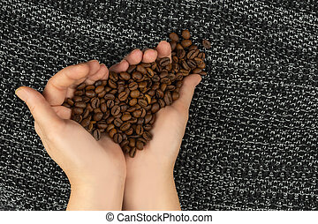 Roasted coffee beans in the palms in the form of a heart top view with copy space