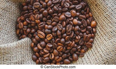 Roasted coffee beans on burlap background. - Natural brown...