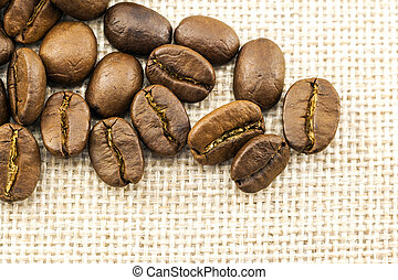 Roasted coffee beans on burlap sackcloth texture background
