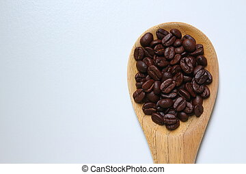Roasted coffee beans on wooden ladle