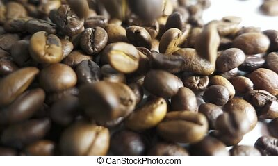 Roasted coffee beans poured in a heap. Slow motion - Roasted...
