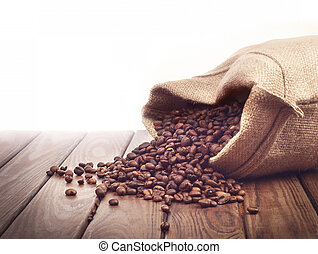 Roasted coffee beans poured out of a sack