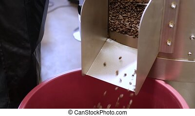 Roasted coffee beans pouring from roaster machine