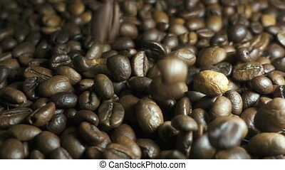 Roasted coffee beans with coffee dust falling down. Slow...