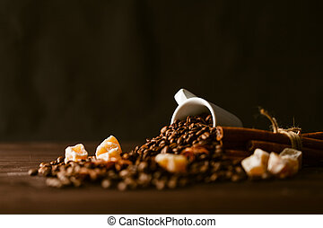 Roasted coffee beans with cup on jute hessian background