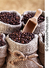 Roasted coffee in bags with wooden scoop on golden background