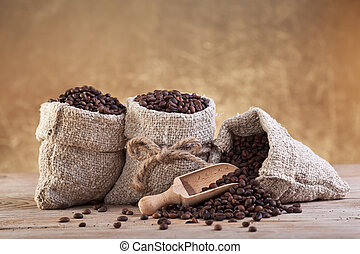 Roasted coffee beans in burlap bags on old wooden table