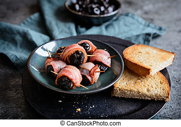 Roasted dried plums wrapped in bacon