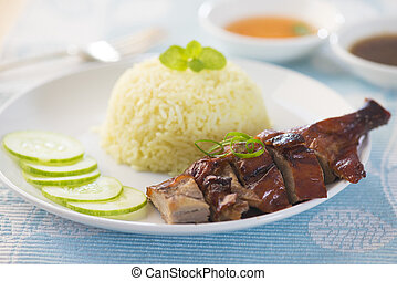 Roasted duck, Chinese style, served with steamed rice on dining table. Singapore cuisine.