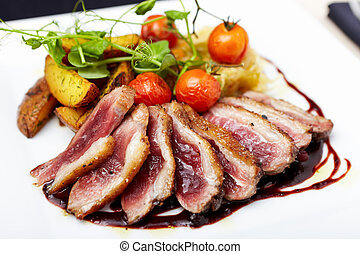 Roasted duck with cherry tomatoes and potatoes marinated in...
