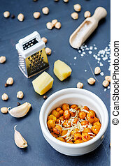 roasted garlic parmesan chickpeas on a black background. the...