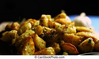 Roasted golden potatoes spiced with fried garlic and rosemary and fresh parsley on a plate. Process of cooking perfect oven roasted potatoes. Artistic shooting.