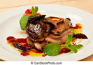 Roasted goose - Roasted sliced goose with mint on dish in...