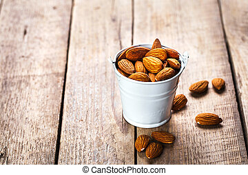 Roasted grains of peanuts in a wooden bucket isolated on white background
