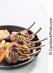 Roasted lamb ribs with vegetables on the white table