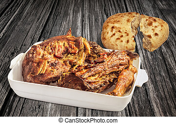 Roasted Lamb Shoulder in White Porcelain Casserole with Leavened Flatbread Halves Set on Old Weathered Cracked Wooden Table Surface