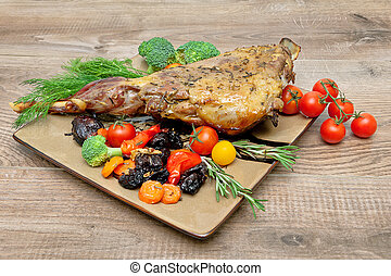 roasted leg of lamb with vegetables, greens and prunes on a plate on a wooden table