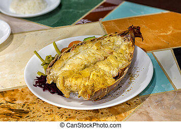 Roasted lobster tail - An open lobster tail served in a...