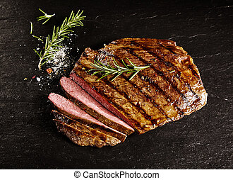 Roasted medium rare sliced flank beef with rosemary - Single...