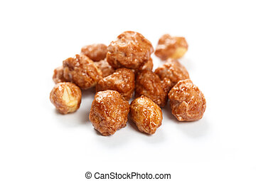 Roasted peanuts in icing sugar close up.