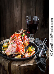 Roasted pheasant with bacon and vegetables on dark background