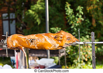 Roasted pig on a traditional spit outdoor on food festival