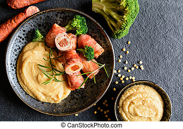 Roasted pork cutlets wrapped in bacon and stuffed with...
