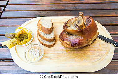 Roasted pork knuckle eisbein with bread and vegetables on wooden cutting board, top view