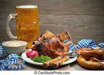 Roasted pork knuckle with pretzels and beer.