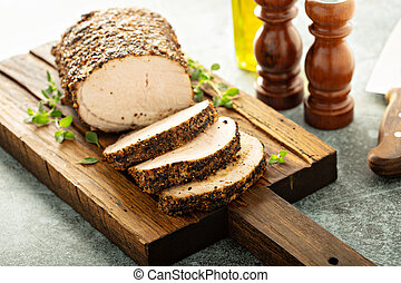 Roasted pork loin with dry rub sliced on a board