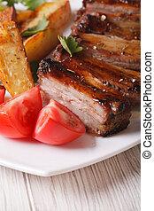 roasted pork ribs, potatoes and tomatoes macro. vertical