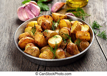 Roasted potato with dill on wooden background
