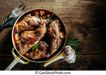 High Angle View of Roasted Rabbit Haunches in Pan with Stewed Vegetables on Rustic Wooden Table Surface with Bulb of Garlic and Copy Space