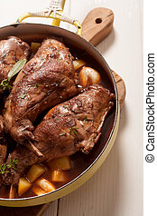 High Angle View of Roasted Rabbit Haunch with Stewed Vegetables in Pan Garnished with Fresh Herbs on Cutting Board
