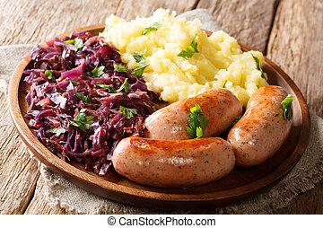 Roasted sausages with steamed cabbage (sauerkraut) and boiled potatoes close-up on a plate. horizontal