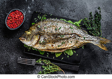 Roasted sea bream fish with herbs on a cutting board. Black background. Top view
