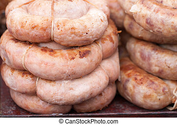 Roasted spiral pork sausages as a background. Selective focus
