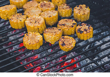 roasted sweet corns on the grill. Burning red coals in the...
