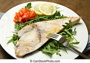 roasted swordfish with lemon, salad and tomatoes on wooden...