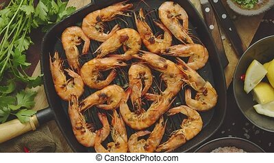 Roasted tiger prawns on iron grilling pan with fresh persley...
