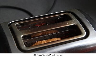 Roasted toast bread popping up of stainless steel.