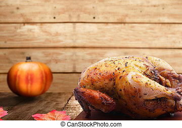 Roasted turkey and pumpkin on wooden table with autumn leaves