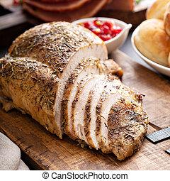 Roasted turkey breast sliced on a board
