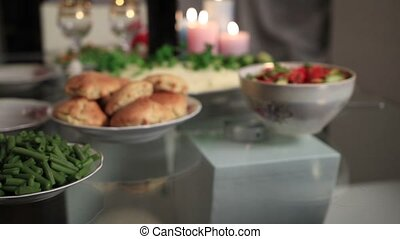 Close up of woman's hand serving roasted turkey with apples and broccoli on platter on Thanksgiving table, decorated with candles and dishes.
