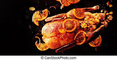 One newly roasted whole chicken garnished with lemon fruit slices on black background